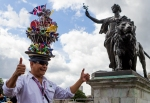 "The Hatman of London, Chito Salarza Grant, displays the hat he made in honor of the 2012 London Olympics in front of Buckingham Palace on Sunday, July 29, 2012 in London. The hat, says Grant, represents the Olympic Stadium and is ""my gift for London and the tourists."" (Anthony L. Solis/Santa Cruz Sentinel)"