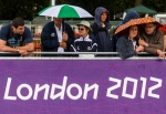 Spectators bring out their umbrellas before the Olympic Women's Road Cycling race in front of Buckingham Palace on Sunday, July 29, 2012 in London. The weather has been fickle since the start of the Games, changing from temperatures in the 80s to being cold and rainy, sometimes in a matter of minutes. (Anthony L. Solis/Santa Cruz Sentinel)